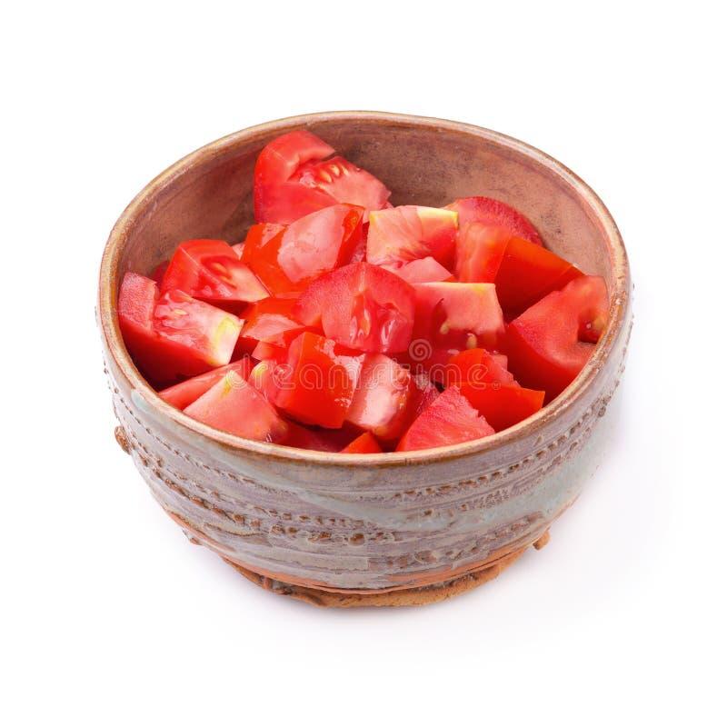 Gehakte tomaten in een kom die op een witte achtergrond wordt geïsoleerd royalty-vrije stock afbeelding
