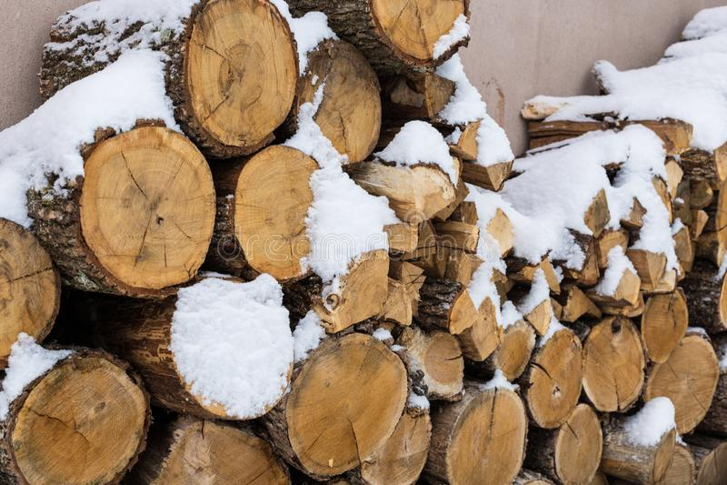 Gehakte voorraad van brandhout onder sneeuw op de straat Brandhout voor open haard en bbq stock foto's