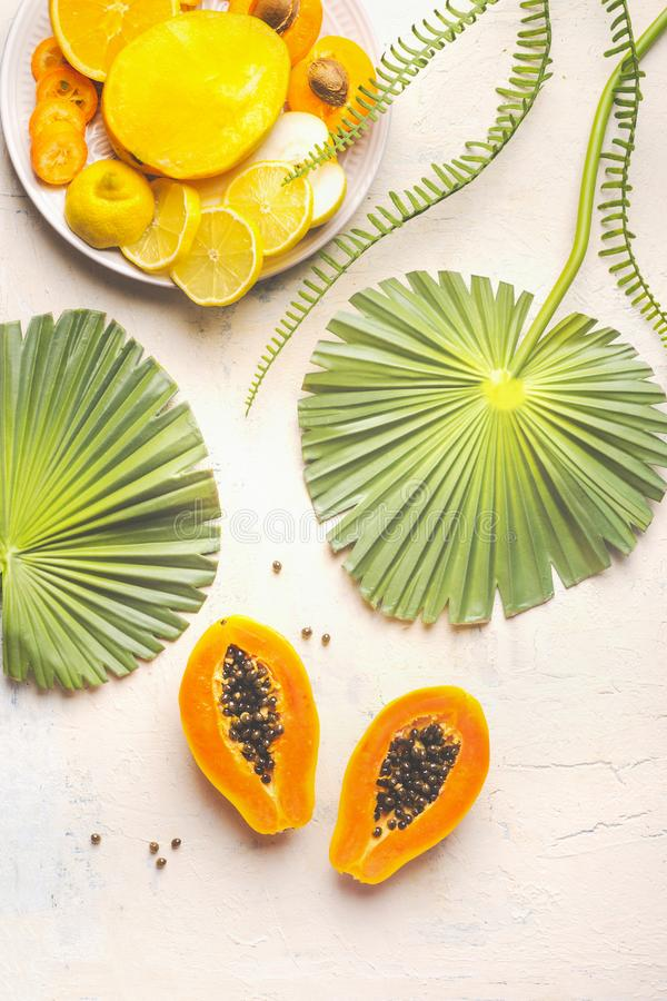 Gehalveerd rijp papajafruit met zaden op witte lijst met tropische bladeren en plaat met gele gesneden vruchten, hoogste mening D stock fotografie