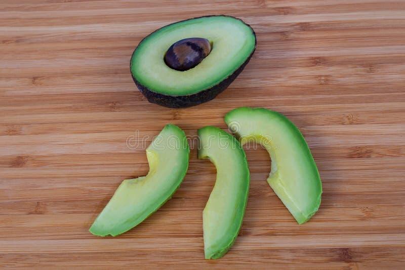 Gehalveerde avocadokuil die drie plakken op natuurlijke achtergrond tonen stock afbeelding