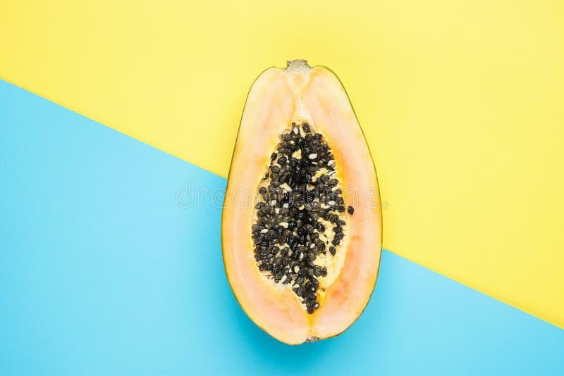 Gehalveerde Rijpe Papaja op de Gespleten Gele Blauwe Achtergrond van Duotone Gestileerd Creatief Beeld Tropische Vruchten het Str stock foto's