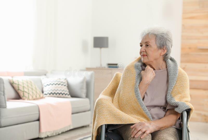 Gehandicapt bejaarde omvat met deken bij verpleeghuis Bijwonende hogere mensen stock fotografie