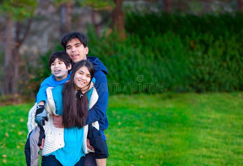 Gehandicapt biracial kind die op de rug op zijn zuster, familie berijden royalty-vrije stock foto's