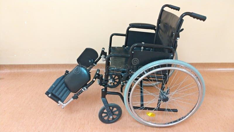 Gehandicapt vervoer Zwarte rolstoel in het ziekenhuis voor het vervoer van ernstig zieke mensen royalty-vrije stock afbeelding