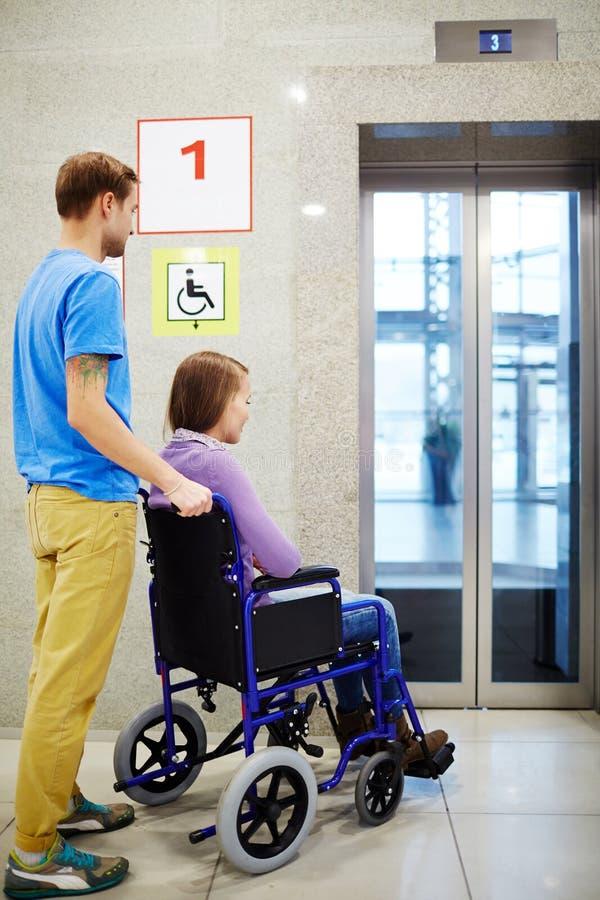 Gehandicapt wachten voor lift stock foto's