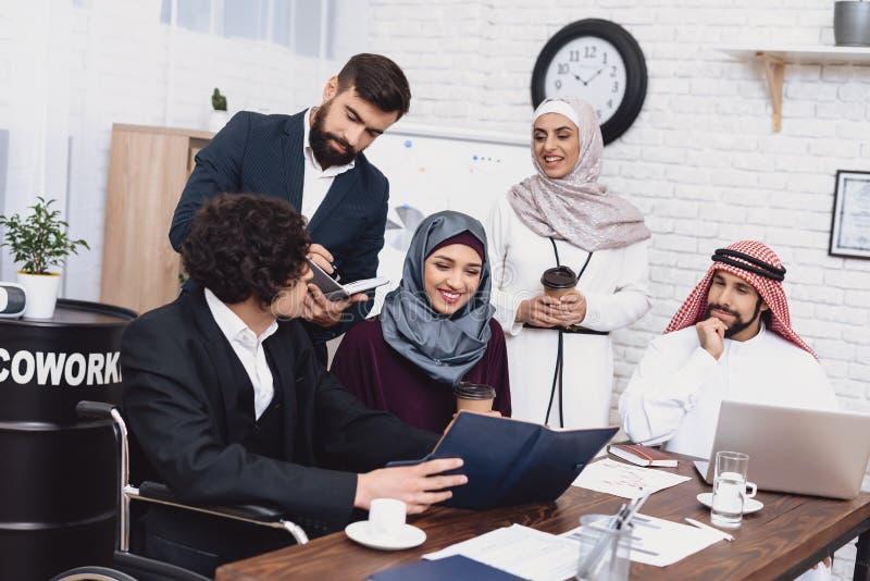 Gehandicapte Arabische mens in rolstoel die in bureau werken De mens deelt nota's met medewerkers royalty-vrije stock foto's