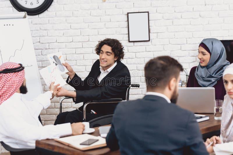 Gehandicapte Arabische mens in rolstoel die in bureau werken De mens doet presentatie voor medewerkers stock afbeeldingen
