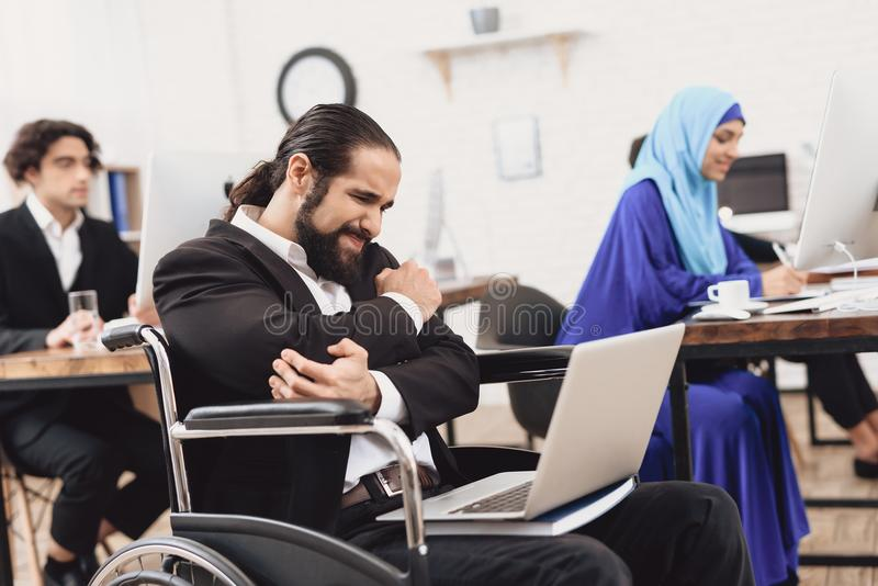 Gehandicapte Arabische mens in rolstoel die in bureau werken De mensen` s elleboog kwetst royalty-vrije stock afbeelding