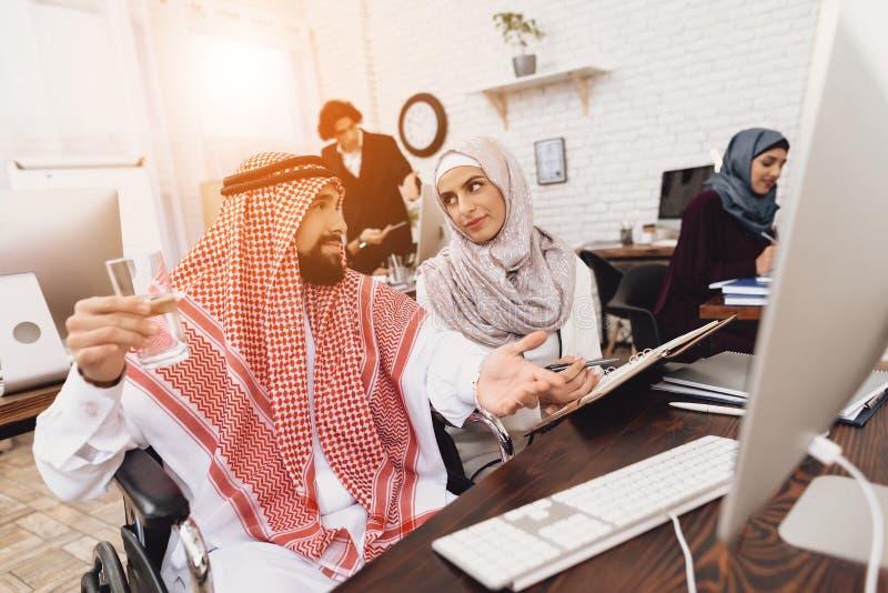 Gehandicapte Arabische mens in rolstoel die in bureau werken De mens neemt nota's met vrouwelijke medewerker stock afbeeldingen