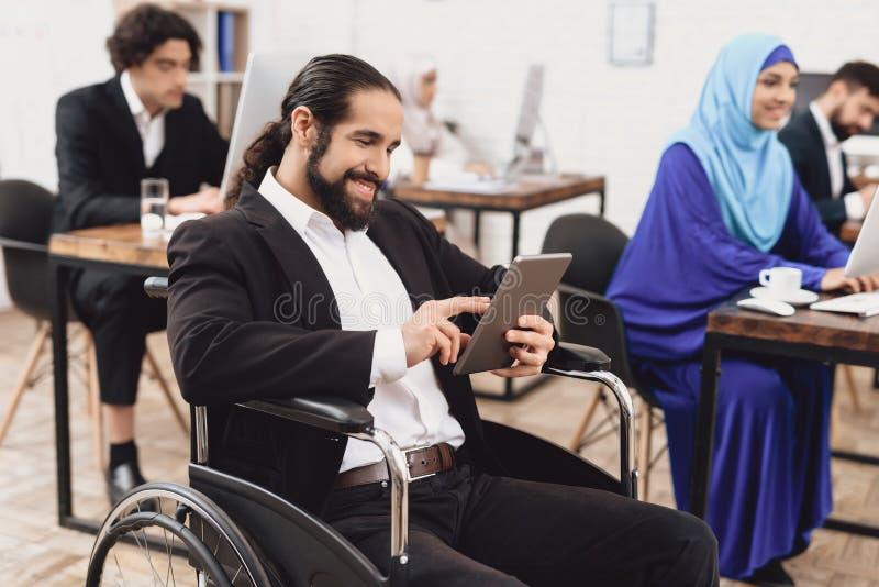 Gehandicapte Arabische mens in rolstoel die in bureau werken De mens spreekt op tablet stock afbeeldingen