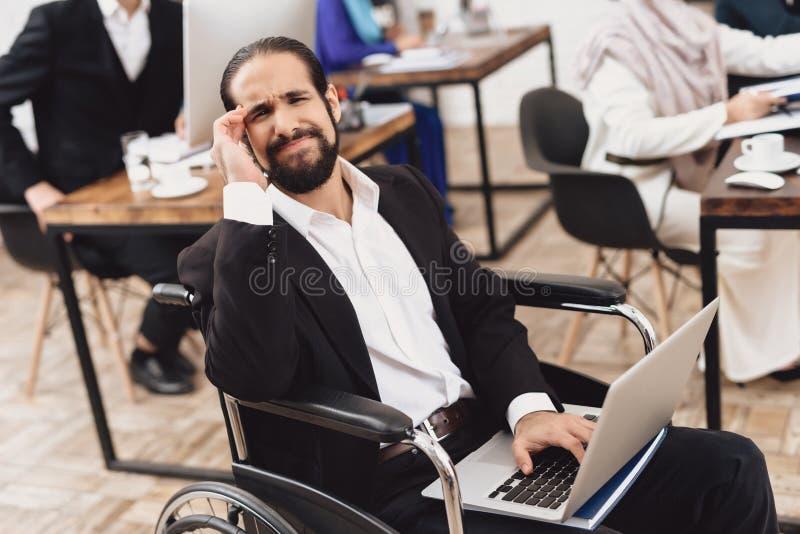 Gehandicapte Arabische mens in rolstoel die in bureau werken Het mensen` s hoofd kwetst stock foto's