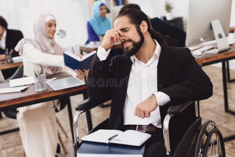 Gehandicapte Arabische mens in rolstoel die in bureau werken Het mensen` s hoofd kwetst stock afbeeldingen