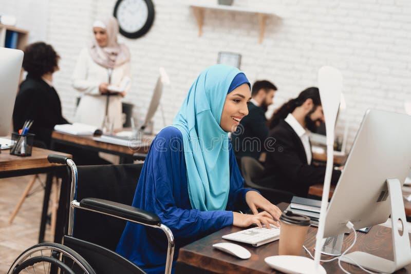 Gehandicapte Arabische vrouw in rolstoel die in bureau werken De vrouw werkt aan bureaucomputer royalty-vrije stock foto