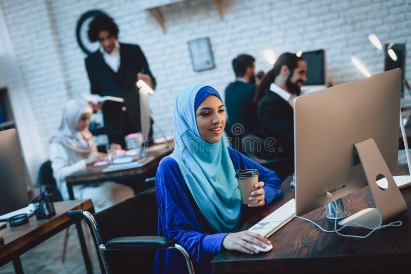 Gehandicapte Arabische vrouw in rolstoel die in bureau werken De vrouw werkt aan bureaucomputer en het drinken koffie royalty-vrije stock fotografie
