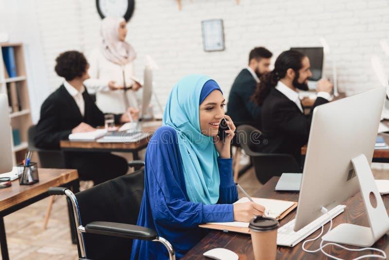 Gehandicapte Arabische vrouw in rolstoel die in bureau werken De vrouw werkt aan bureaucomputer en spreekt op telefoon stock afbeeldingen