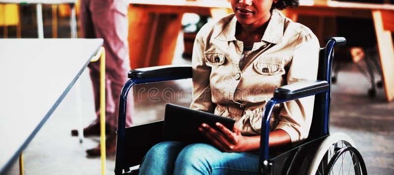 Gehandicapte directeur in rolstoel die digitale tablet gebruiken stock afbeelding