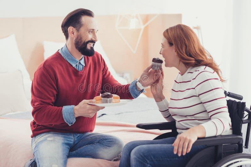 Gehandicapte een smakelijke cake bijten en vrouw die gelukkig voelen royalty-vrije stock afbeelding