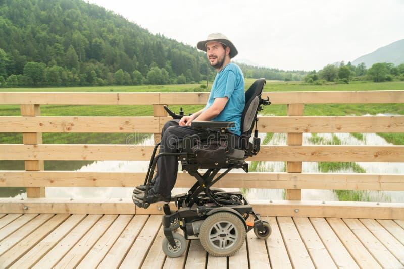 Gehandicapte gelukkige jonge mens in elektrische rolstoel op een promenade die van zijn vrijheid en het glimlachen genieten stock fotografie