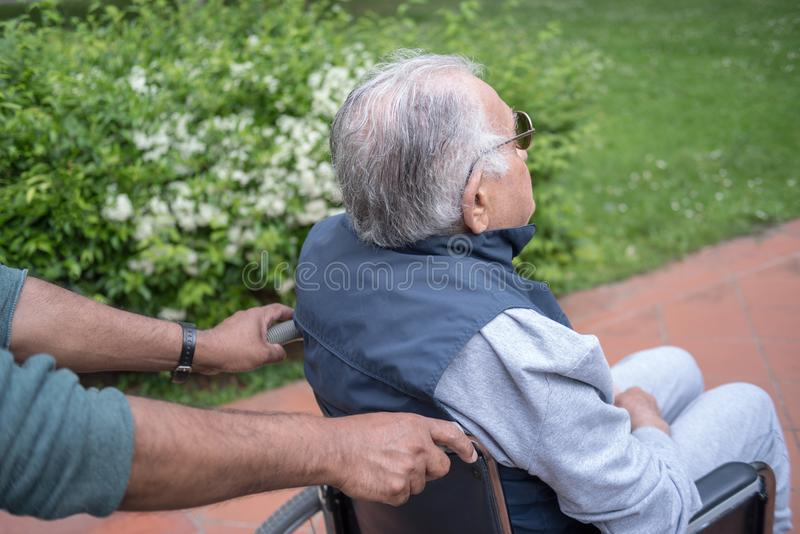 Gehandicapte hogere mens in rolstoel openlucht royalty-vrije stock fotografie