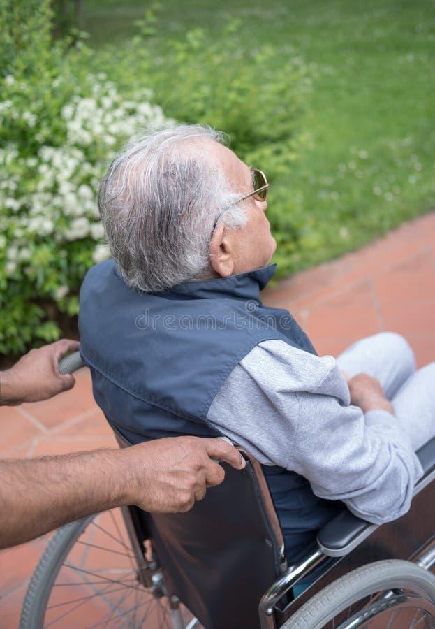 Gehandicapte hogere mens in rolstoel openlucht stock afbeeldingen