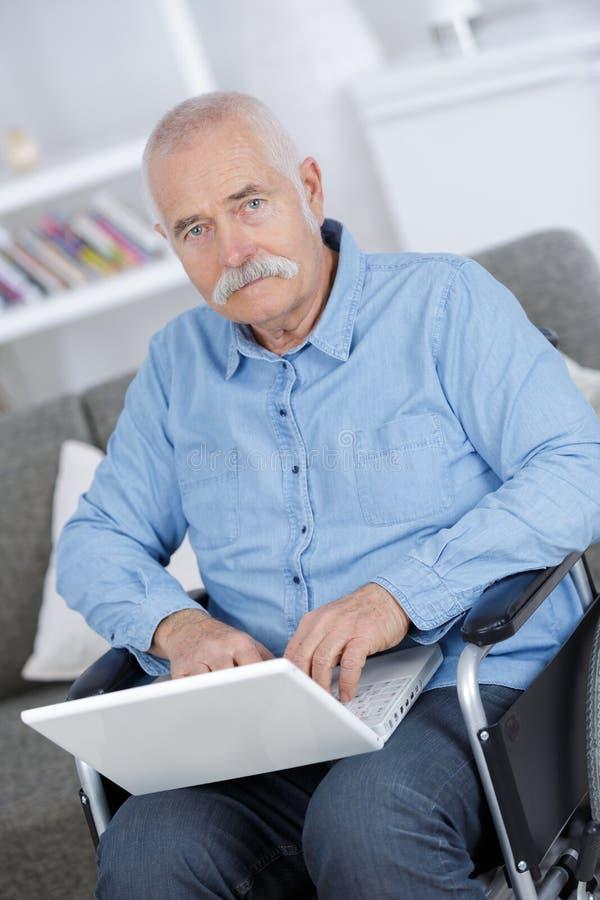 Gehandicapte hogere mensenzitting in rolstoel die laptop met behulp van royalty-vrije stock foto