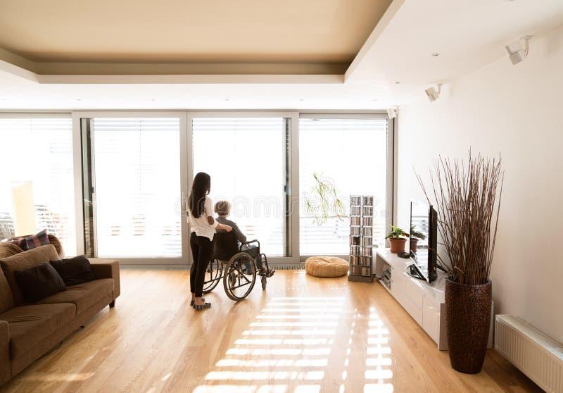 Gehandicapte hogere vrouw in rolstoel met haar jonge daugher stock foto