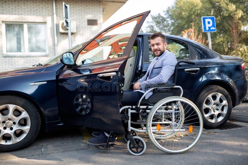 Gehandicapte jonge mens die voor zijn auto bereiken royalty-vrije stock afbeelding