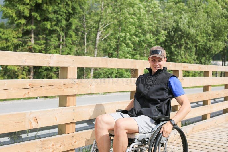 Gehandicapte jonge mens op een rolstoel royalty-vrije stock afbeeldingen