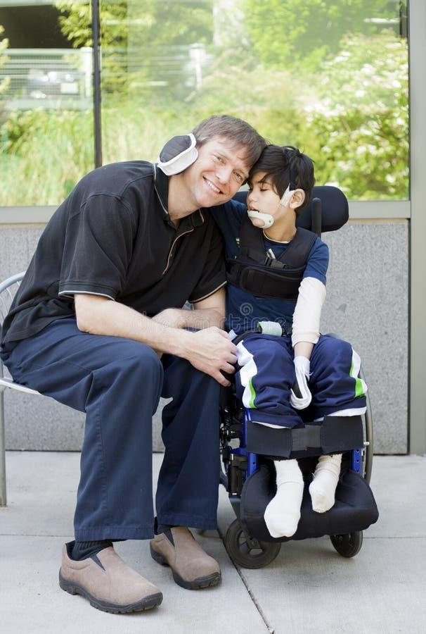 Gehandicapte jongen die vader koesteren terwijl het wachten bij het ziekenhuis royalty-vrije stock afbeeldingen