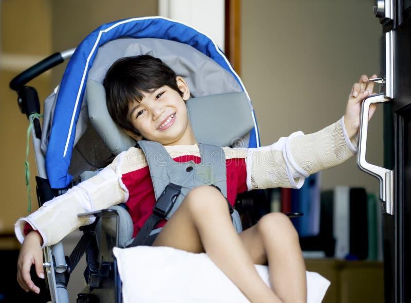 Gehandicapte jongen in rolstoel openingsdeur stock afbeeldingen