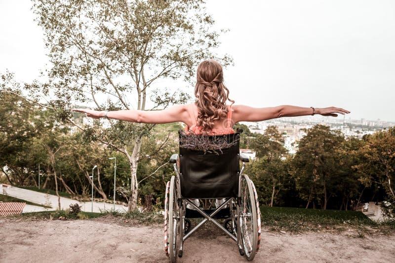Gehandicapte meisjeszitting in de rolstoel en het doen van oefeningen royalty-vrije stock afbeeldingen