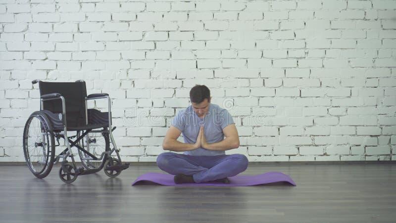 Gehandicapte mens die yoga, rolstoel en oefeningsmat doen stock foto