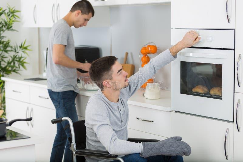 Gehandicapte mens en vriend die maaltijd in keuken voorbereiden royalty-vrije stock afbeeldingen