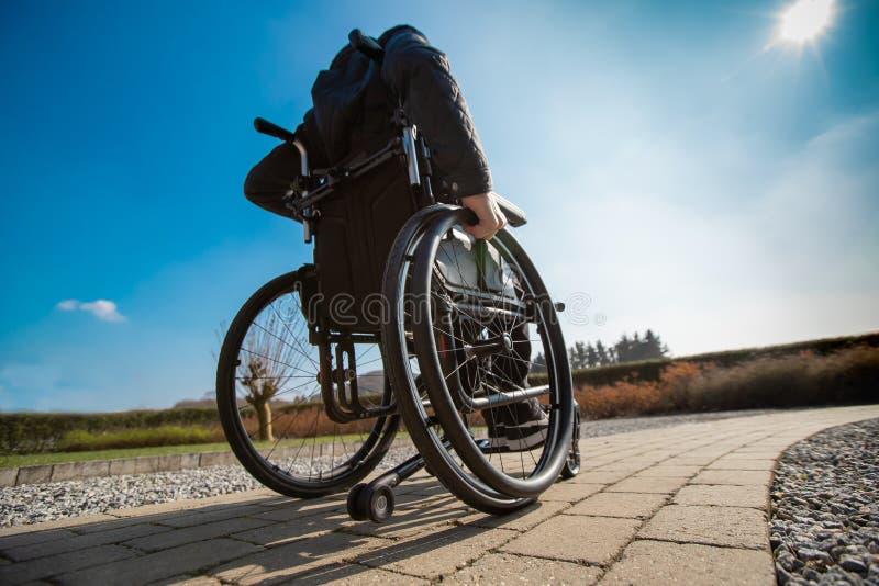Gehandicapte mens in het wheelchar drijven in de zon royalty-vrije stock foto
