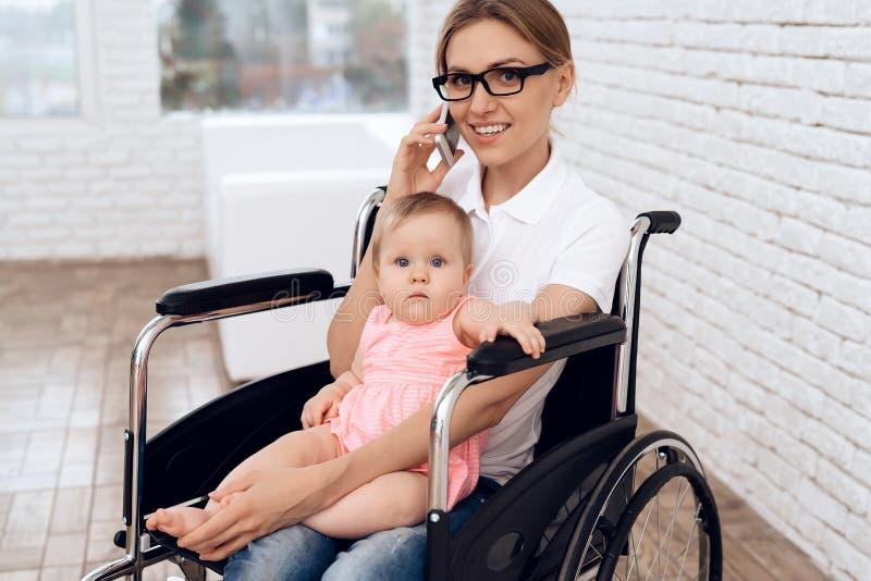 Gehandicapte moeder in rolstoel het werk met pasgeboren stock fotografie