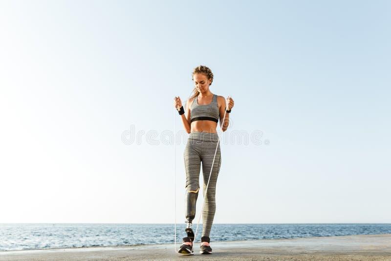 Gehandicapte sportenvrouw die met touwtjespringen springen stock fotografie