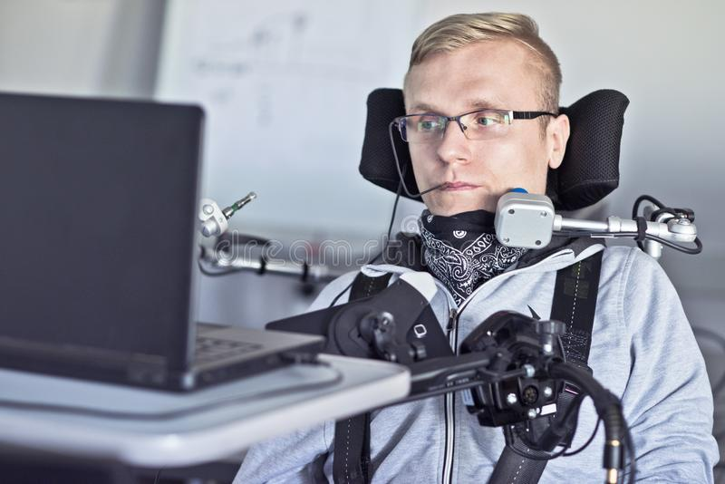 Gehandicapte student die met zijn computer werken stock afbeeldingen