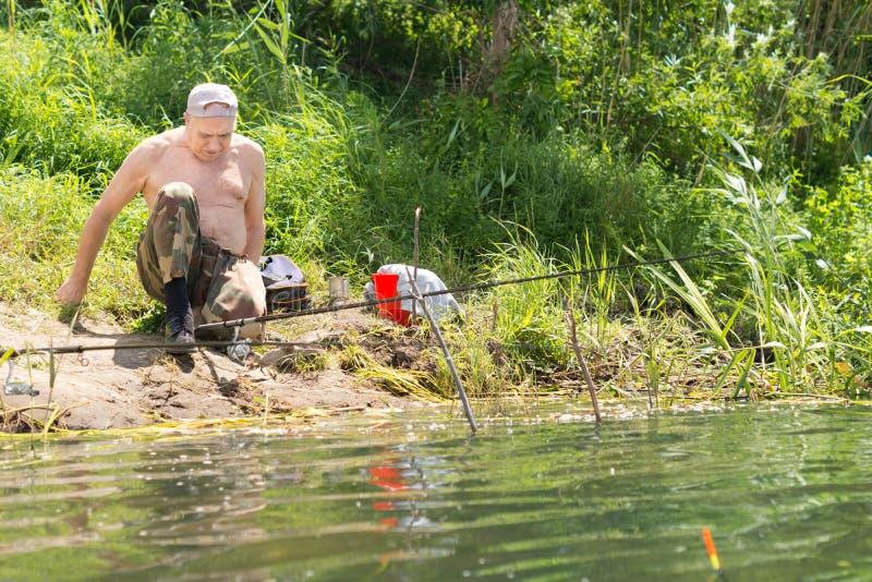 Gehandicapte visser die zijn zittingspositie aanpassen royalty-vrije stock fotografie