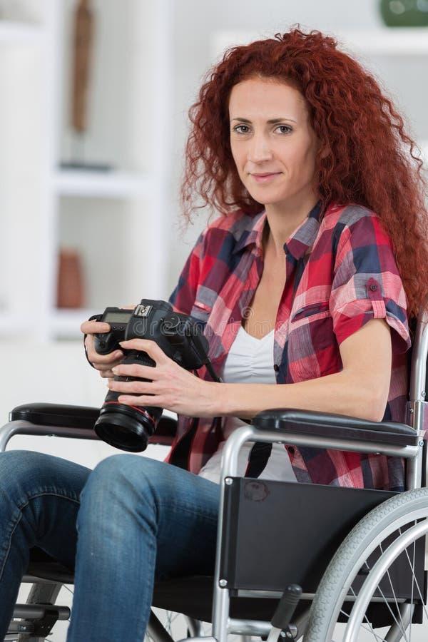 Gehandicapte vrouw die beelden met dslrcamera nemen stock foto