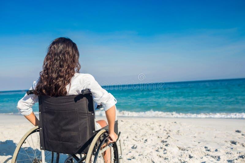 Gehandicapte vrouw die de oceaan bekijken stock foto