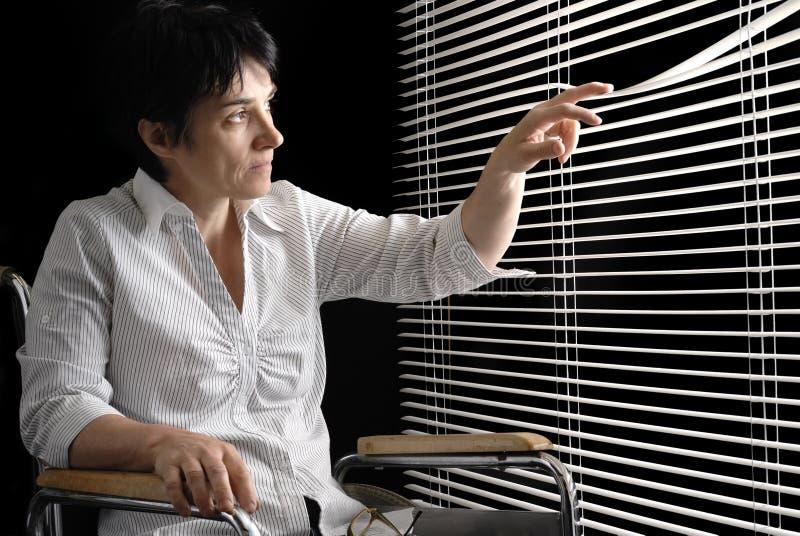 Gehandicapte vrouw die in rolstoel trogzonneblinden kijkt stock afbeelding