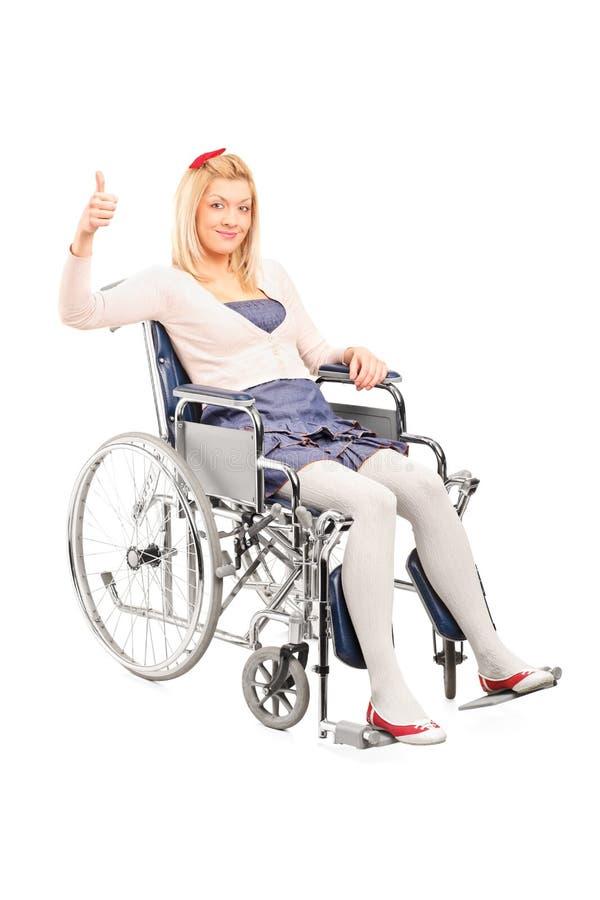Gehandicapte vrouw in een rolstoel die duim opgeven stock afbeelding