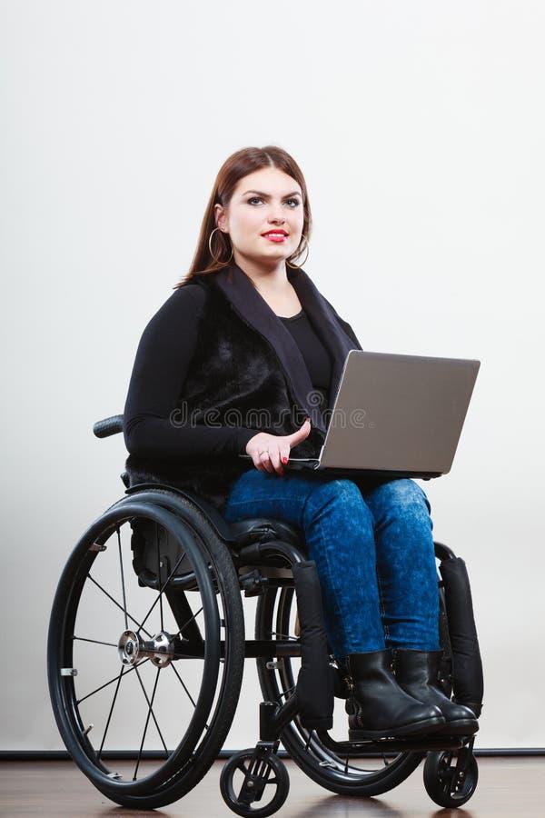 Gehandicapte vrouw met laptop op rolstoel stock foto's