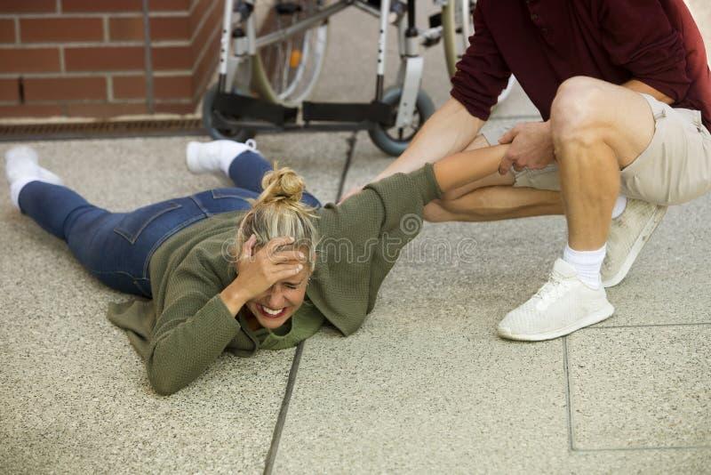 Gehandicapte vrouw op bestrating naast rolstoel die hulp krijgen stock foto