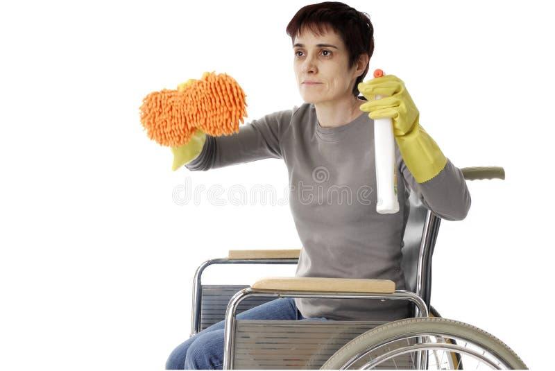 Gehandicapte vrouw in rolstoel die het schoonmaken doet royalty-vrije stock foto