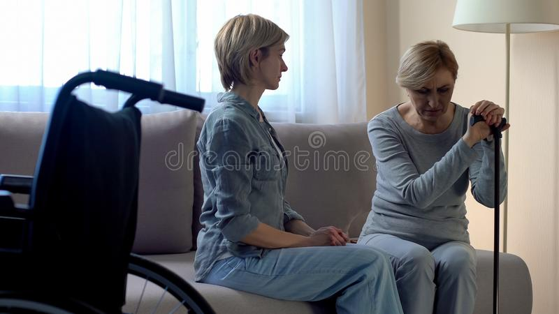 Gehandicapte vrouw uitgeput na rehabilitatieprocedures, die met verpleegster spreken royalty-vrije stock afbeeldingen