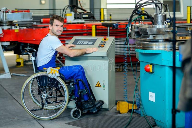 Gehandicapte werknemer in rolstoel in fabriek royalty-vrije stock afbeelding