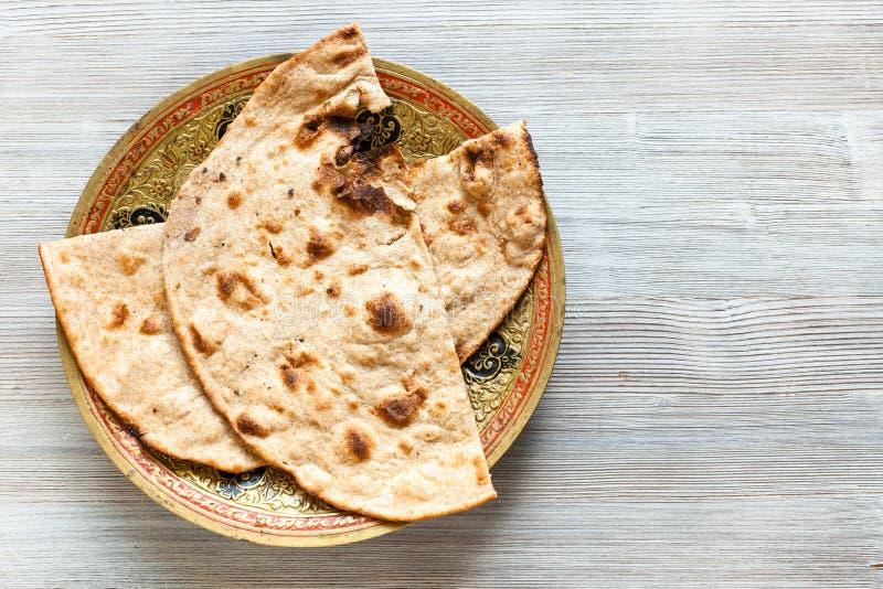 Geheel de tarwe vlak brood van Tandooriroti op grijze lijst stock foto