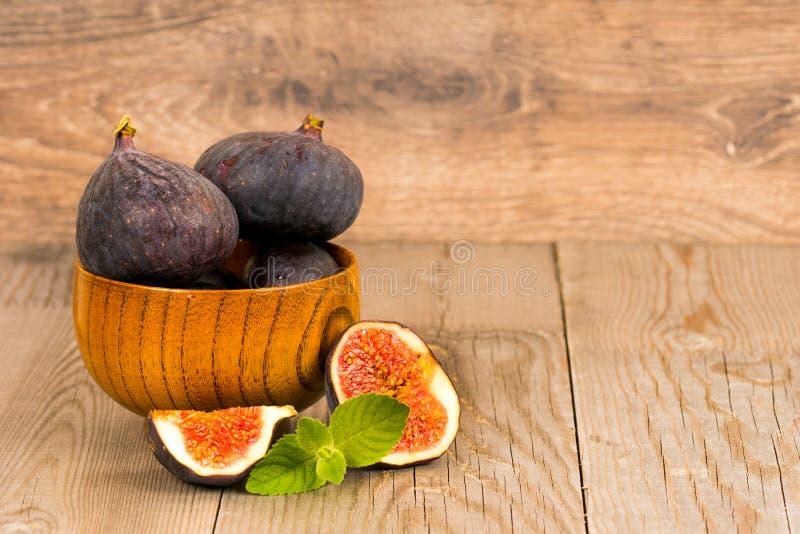 Geheel en besnoeiings verse fig.vruchten in houten plaat stock afbeelding