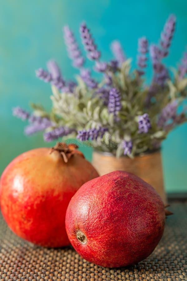 Geheel granaatappels en boeket van bloemenlavendel van close-up op een mooie rustieke lijst royalty-vrije stock afbeeldingen